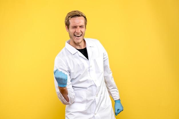 黄色の背景の健康薬のパンデミックを喜んでいる正面図の男性医師