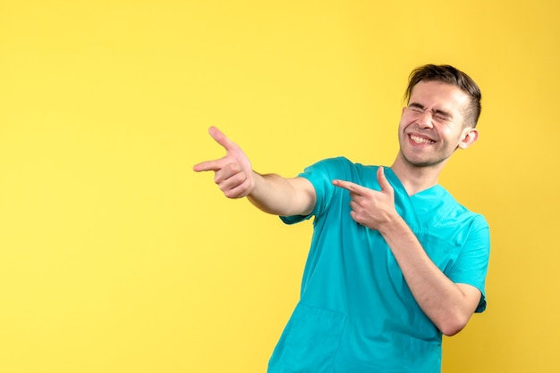 Front view of male doctor laughing on yellow wall