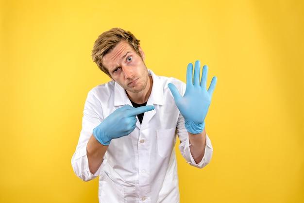 Medico maschio vista frontale su sfondo giallo chiaro medic covid-igiene sanitaria
