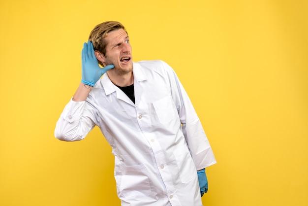Вид спереди мужской доктор, слушающий на желтом фоне, пандемия здоровья медика