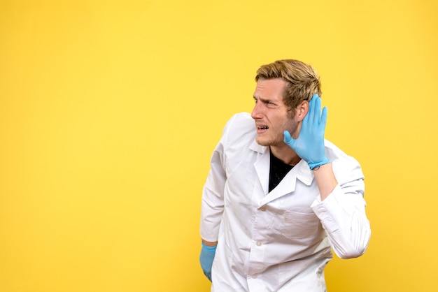 Front view male doctor listening on yellow background covid- pandemic health medic