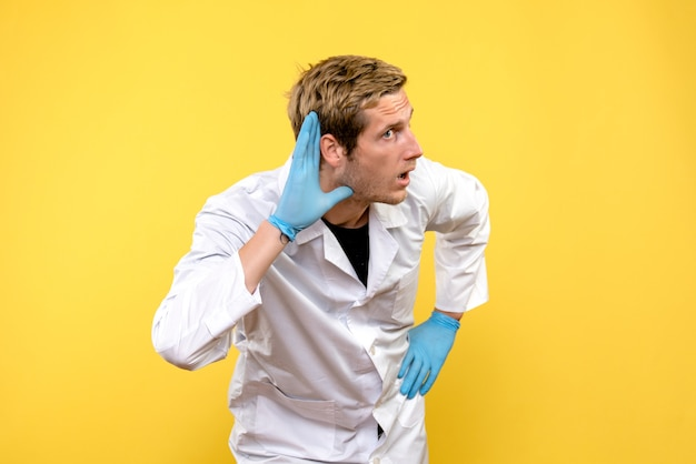 Front view male doctor listening on a yellow background health covid- pandemic medic