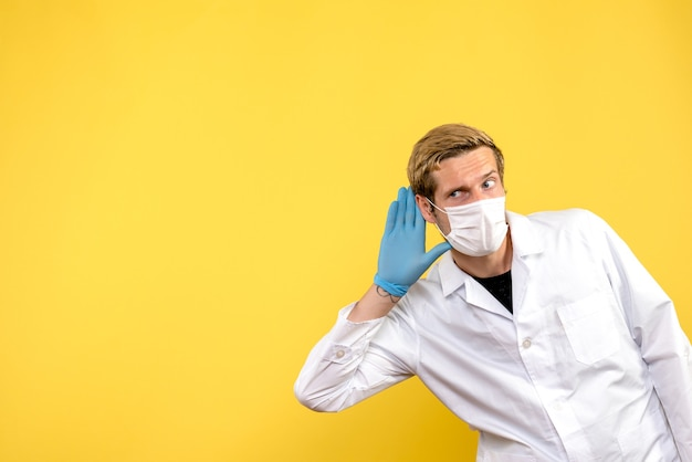 Front view male doctor listening on yellow background pandemic medic health covid- virus