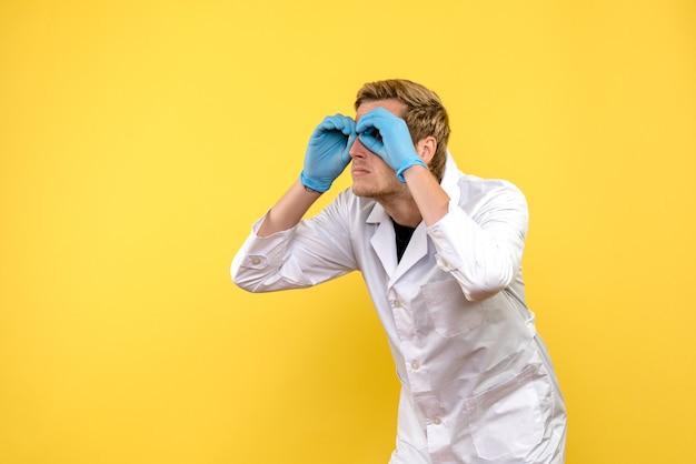 黄色の背景で指を通して見ている正面図の男性医師