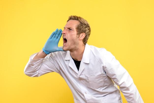 Вид спереди мужчина-врач громко зовет на желтом фоне пандемия человека covid medic