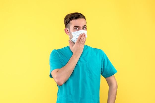 Vista frontale del medico maschio in maschera sul muro giallo chiaro