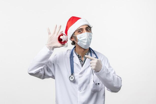 Medico maschio di vista frontale in maschera con il giocattolo su un nuovo anno di salute covid del virus della parete bianca