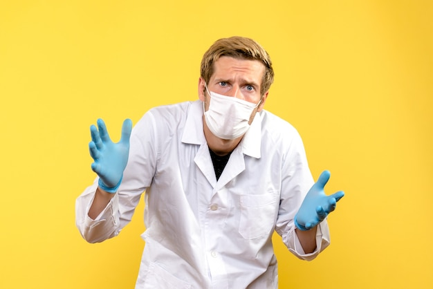 Medico maschio vista frontale in maschera su sfondo giallo medico pandemia covid-salute