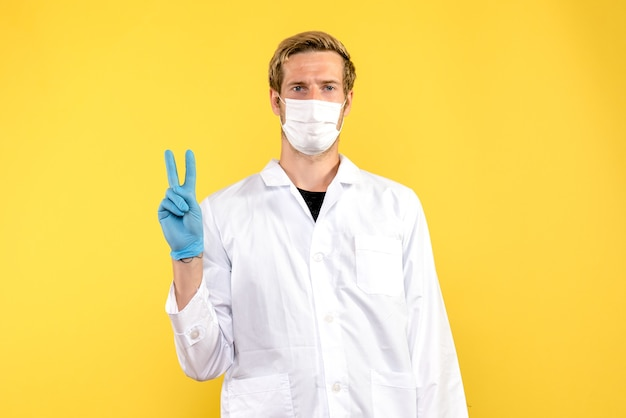 Front view male doctor in mask on yellow background health covid- medic pandemic