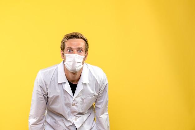 Medico maschio vista frontale in maschera su sfondo giallo virus della pandemia covid-salute
