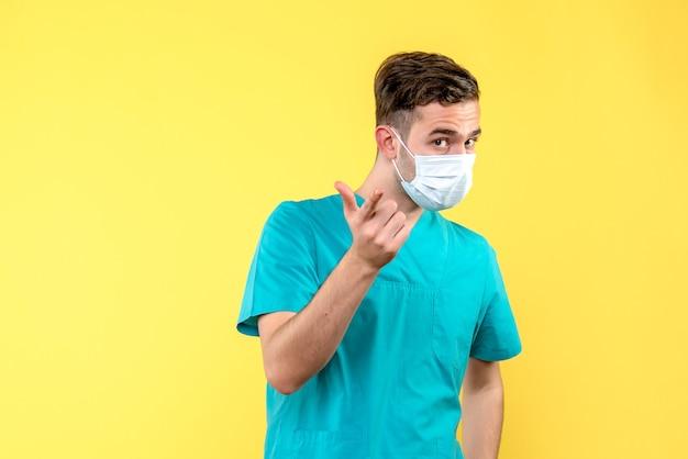 Vista frontale del medico maschio in maschera sul pavimento giallo medic virus salute covid