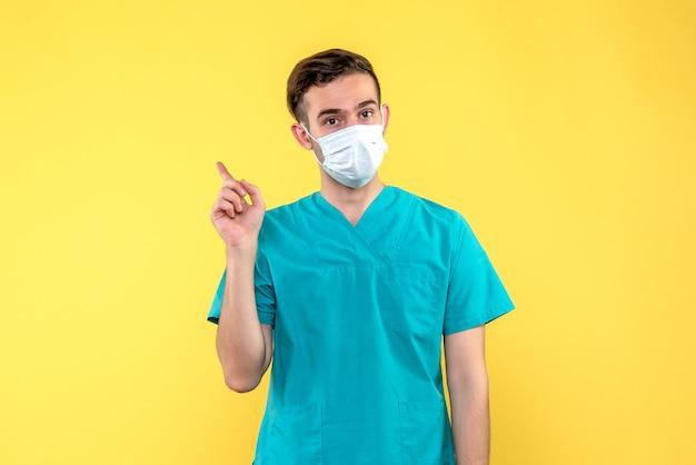 Vista frontale del medico maschio in maschera sulla parete gialla