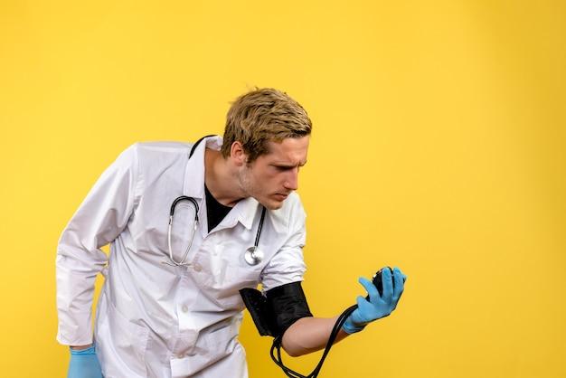 Medico maschio di vista frontale che misura la sua pressione sul virus giallo dell'erba medica dello scrittorio