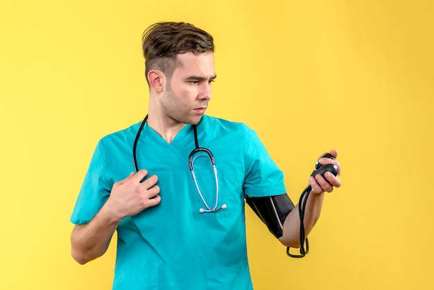 Front view of male doctor measuring pressure on the yellow wall