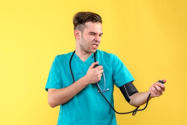 Vista frontale del medico maschio che misura la pressione sulla parete gialla
