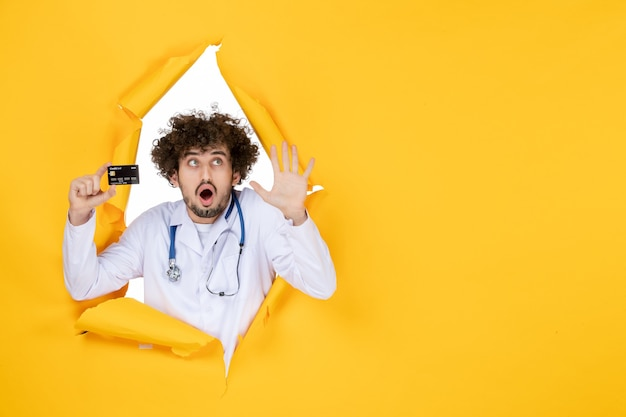 Medico maschio di vista frontale in vestito medico che tiene la carta di credito sul virus di salute della malattia dell'ospedale di medicina di colore strappato giallo