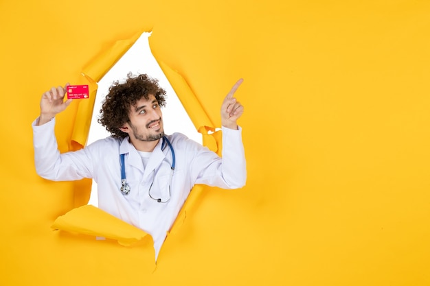Front view male doctor in medical suit holding red bank card on yellow color medicine hospital disease virus medic money health