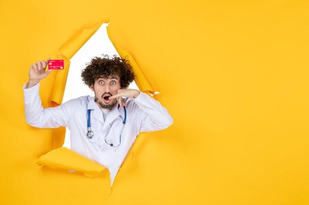 Vista frontale medico maschio in tuta medica con carta di credito rossa su colori gialli medicina ospedale malattia salute virus medico denaro