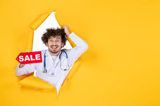 Medico maschio di vista frontale in vestito medico che tiene la scrittura di vendita sul colore giallo che compera la medicina dell'ospedale di salute del medico
