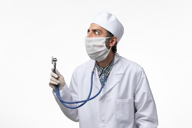 Medico maschio di vista frontale in vestito e maschera medici a causa dello stetoscopio della tenuta del coronavirus sulla scrivania bianca