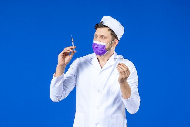 Front view of male doctor in medical suit and mask filling injection with vaccine on blue