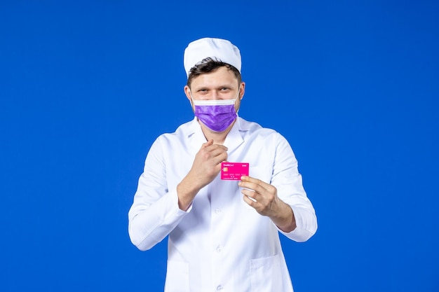 Front view of male doctor in medical suit and mask holding credit card on blue