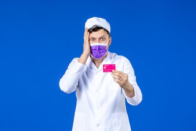 Vista frontale del medico maschio in tuta medica e maschera che tiene la carta di credito sull'azzurro
