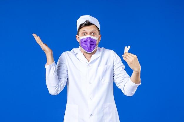 Vista frontale del medico maschio in tuta medica e maschera che tiene piccoli cerotti medici sull'azzurro