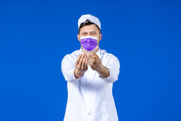 Vista frontale del medico maschio in tuta medica e maschera che tiene vaccino e iniezione sull'azzurro