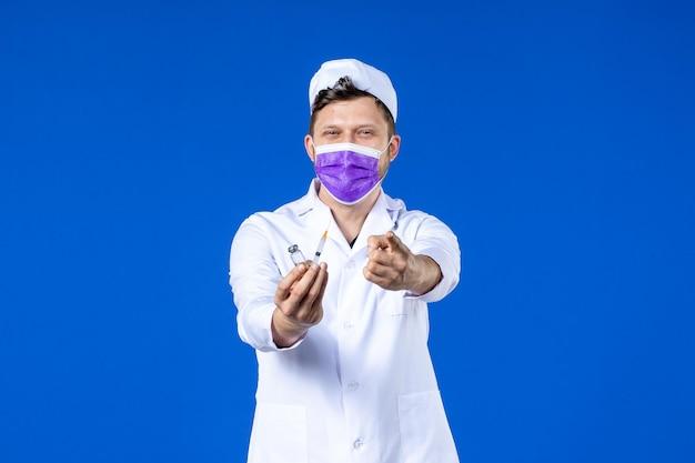 Vista frontale del medico maschio in tuta medica e maschera con iniezione e vaccino sull'azzurro
