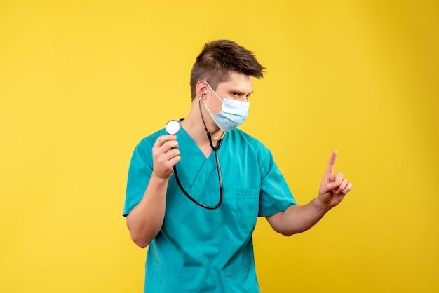 Vista frontale del medico maschio in tuta medica e maschera con lo stetoscopio sulla parete gialla