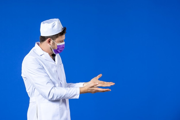 Front view of male doctor in medical suit and purple mask on blue