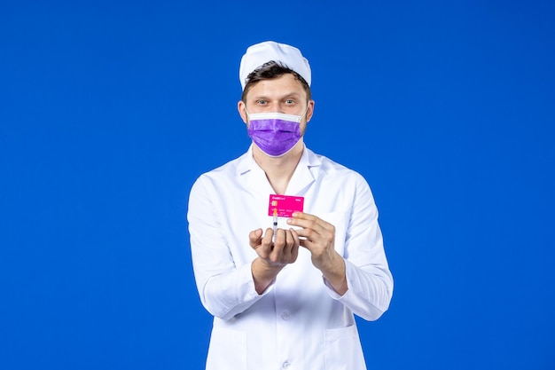 Front view of male doctor in medical suit and purple mask holding injection and credit card on blue