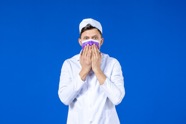 Front view of male doctor in medical suit and purple mask sending kisses on blue