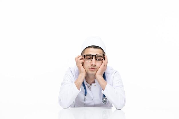 Medico maschio di vista frontale in vestito medico che si siede dietro la scrivania