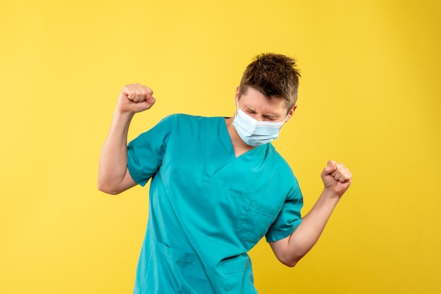 Front view of male doctor in medical suit and sterile mask rejoicing on yellow wall