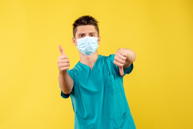 Front view of male doctor in medical suit and sterile mask on the yellow wall