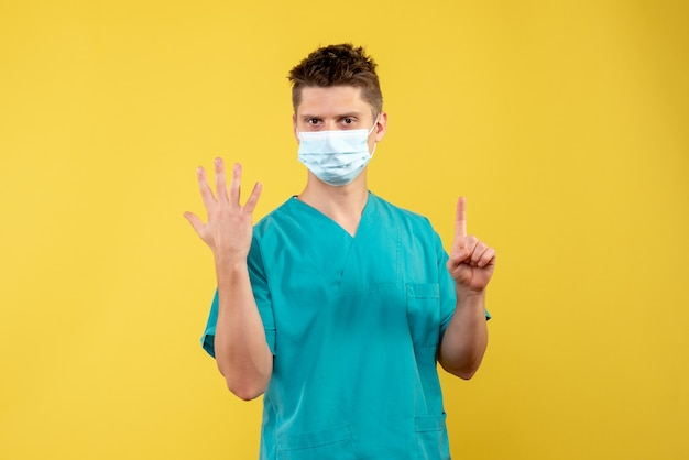 Vista frontale del medico maschio in tuta medica e maschera sterile sulla parete gialla