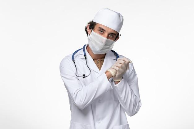 Vista frontale medico maschio in tuta medica e indossa una maschera come protezione da covid- sulla scrivania bianca malattia virus covid- pandemia