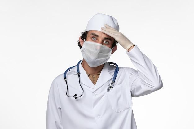 Vista frontale medico maschio in tuta medica e indossa una maschera come protezione dalla pandemia covid-on white wall virus covid