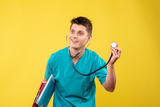 Vista frontale del medico maschio in tuta medica con analisi e stetoscopio sulla parete gialla