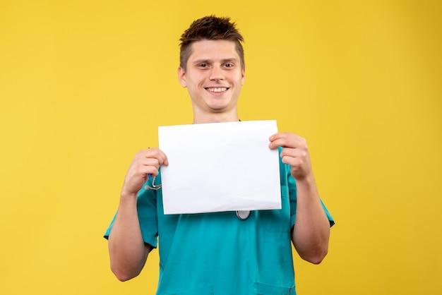 Vista frontale del medico maschio in tuta medica con analisi sulla parete gialla