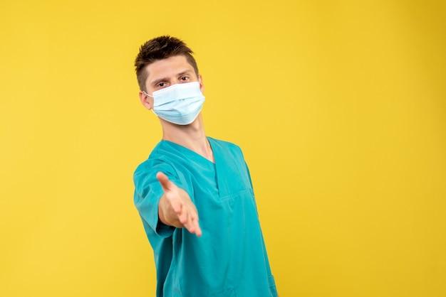 Vista frontale del medico maschio in tuta medica con maschera sterile saluto sulla parete gialla