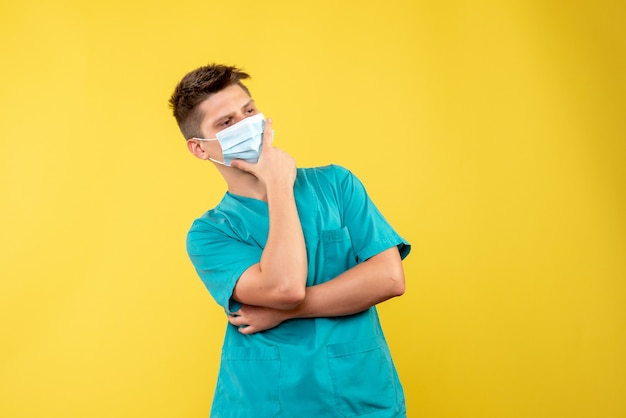 Front view of male doctor in medical suit with sterile mask thinking on yellow wall