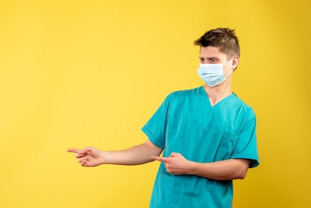 Vista frontale del medico maschio in tuta medica con maschera sterile sulla parete gialla