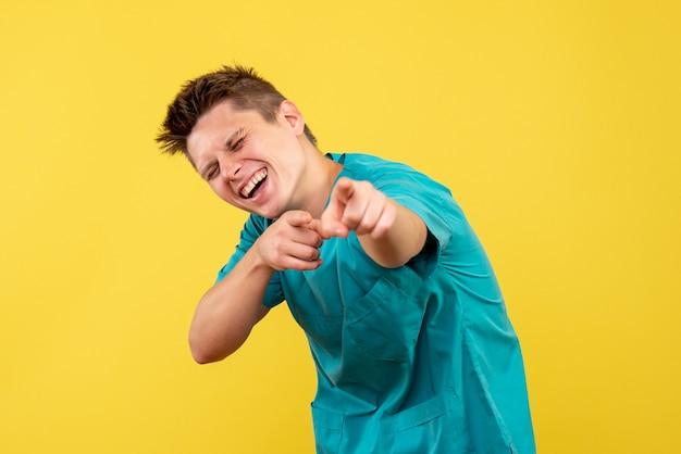 Vista frontale del medico maschio in tuta medica sulla parete gialla