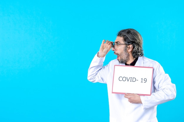 Front view male doctor in medical uniform holding covid- writing on blue