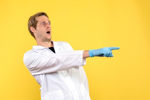 黄色の背景に神経質な正面図男性医師人間のcovid-病院の薬