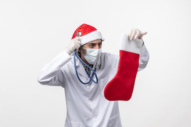 白い机の上の休日の靴下を観察する正面図男性医師covidウイルス休日の健康