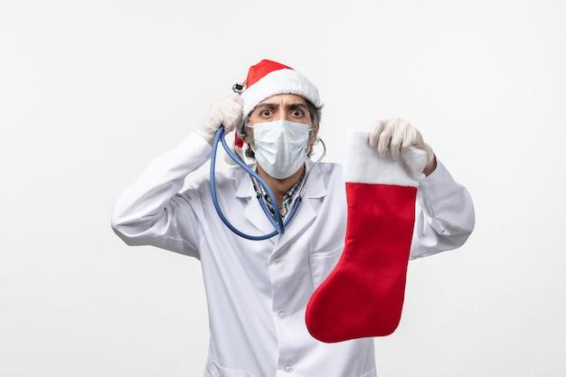 Вид спереди мужчина-врач, наблюдающий за праздничным носком на белом полу, вирус covid, здоровье праздника